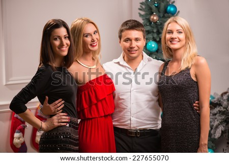 Half-length portrait of the group of happy smiling friends standing together hugging each other waiting for the New Year - stock photo
