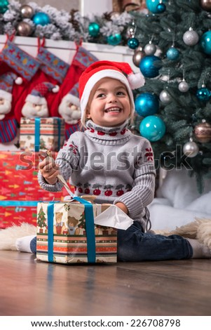 Half-length portrait of the little cute fair-haired smiling girl sitting on the floor near Christmas presents wearing warm sweater and red cap of Santa Claus wanted to unpack her nice present - stock photo