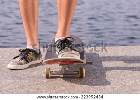 Half-length portrait of the man wearing shorts and trainers riding a skateboard on the quay - stock photo