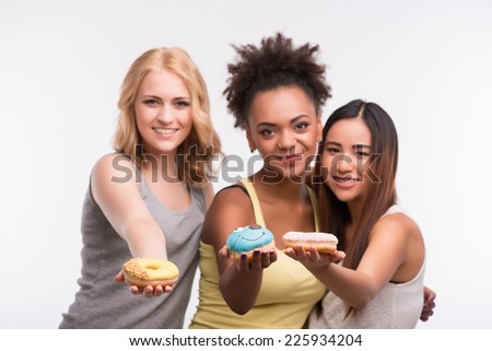 Half-length portrait of three beautiful tempting girls wearing colorful T-shirts having fun proposing us to taste bright delicious doughnuts. Isolated on white background - stock photo