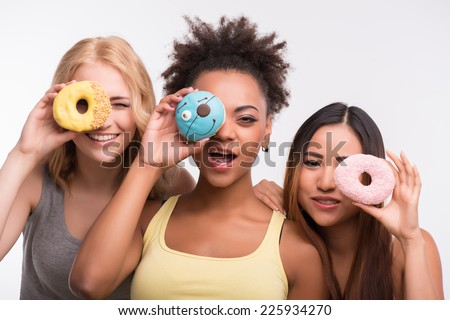 Half-length portrait of three beautiful tempting girls wearing colorful T-shirts having fun looking through the bright delicious doughnuts. Isolated on white background - stock photo