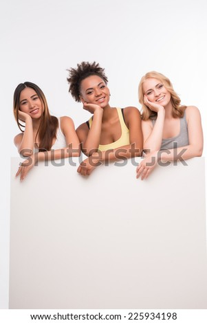 Half-length portrait of three young lovely smiling girls wearing colorful T-shirts and jeans looking out of the big white poster for copy place leaning on it. Isolated on white background - stock photo