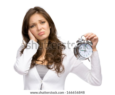 Half-length portrait of tired woman handing alarm clock, isolated on white - stock photo