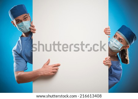 Half-length portrait of two doctors wearing blue medical uniform and masks looking out of the huge poster for copy place showing us something on it. Isolated on blue background - stock photo