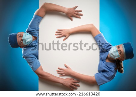 Half-length portrait of two doctors wearing blue medical uniform and masks looking out of the huge white poster for copy place putting their hands on it. Isolated on blue background. Top view - stock photo
