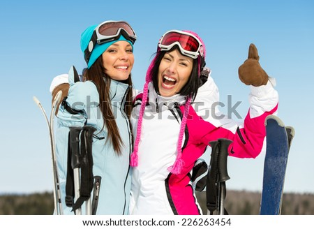 Half-length portrait of two female downhill skier friends thumbing up - stock photo