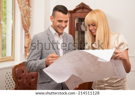 Half-length portrait of two young attractive architects discussing design project holding architectural plan in studio laughing, classical interior background - stock photo