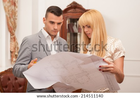 Half-length portrait of two young attractive architects discussing design project holding architectural plan in studio, classical interior background - stock photo