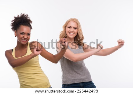 Half-length portrait of two young pretty smiling women wearing colorful T-shirts having a fun dancing. Isolated on white background - stock photo