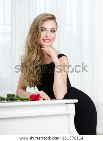 Half-length portrait of woman in black dress standing near the piano with red rose on it. Concept of music and art - stock photo