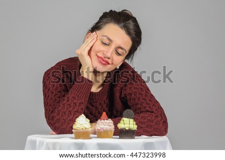 Half-length portrait of woman in burgundy sweater looking on piece of tasty chocolate cake, on gray background