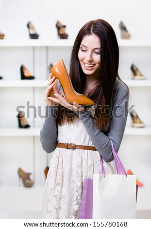 Half-length portrait of woman keeping brown leather heeled shoe in shopping center