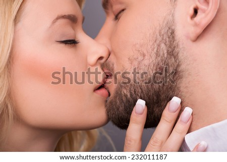 Half-length portrait of young beautiful couple standing with closed eyes facing each other kissing. Isolated on dark background