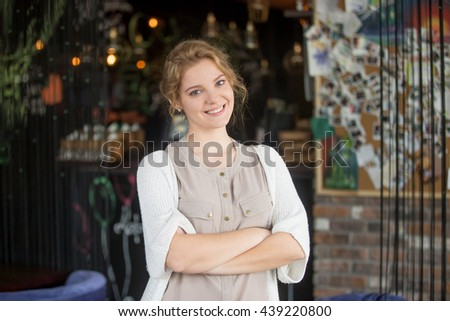 Half-length portrait of young beautiful female standing at her work place with crossed arms. Woman welcoming customers at her own coffee shop. Attractive model posing with arms folded on chest - stock photo