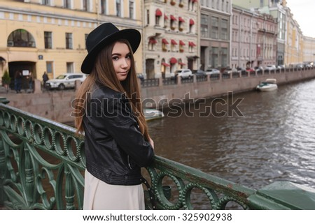 Half length portrait of young charming woman dressed in trendy clothes posing while standing on a river bridge, pretty hipster girl with stylish look relaxing after walking in beautiful urban setting - stock photo
