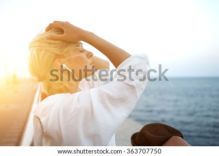 Half length portrait of young charming woman in headphones relaxing while sitting near ocean in summer evening, attractive carefree female listening favorite music during recreation time in weekend - stock photo