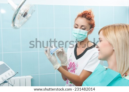 Half-length portrait of young fair-haired lovely smiling girl sitting on the dentist chair looking at the doctor wearing a mask which is showing her false tooth - stock photo