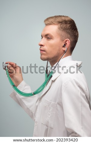 Half length portrait of young handsome doctor, standing side-ways, trying new stethoscope and thinking laboriously.
