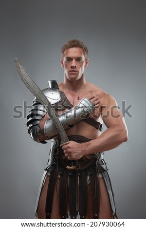 Half length portrait of young handsome muscular man gladiator in armour posing with his arms crossed holding sword isolated over grey background - stock photo