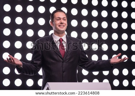 Half- length portrait of young handsome smiling TV presenter wearing great black suit and vinous tie standing behind the rostrum announcing the opening speech - stock photo