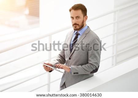 Half length portrait of young man executive director using digital tablet while standing in modern office interior, professional male employer holding touch pad before important meeting with staff - stock photo