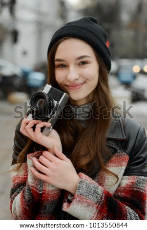 Half-length portrait of young photographer with her camera in city. Creative and artistic person. Hobby and activity.