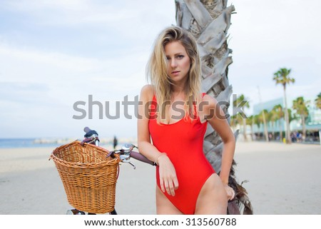 Half length portrait of young sexy woman dressed in trendy swimsuit standing on the beach with her vintage bike, attractive female in swimwear enjoying rest in summer holidays strolling with bicycle - stock photo