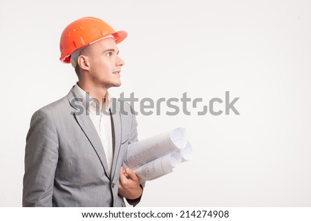 Half-length portrait of young smiling handsome architect engineer in orange helmet posing with blueprints looking sideways isolated on white background, copyspace - stock photo