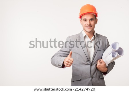 Half-length portrait of young smiling handsome architect engineer in orange helmet posing with blueprints showing thumb up isolated on white background, copyspace - stock photo