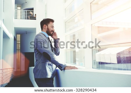 Half length portrait of young successful business man having cell telephone conversation while standing in office interior, male professional banker in suit talking on mobile phone during work break  - stock photo