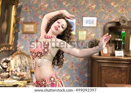 Half-length portrait of young woman dressed in oriental style costume dancing in old-fashioned room.