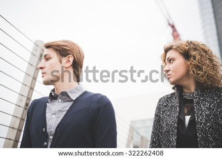 Half length profile of a couple of young handsome caucasian business man and woman overlooking posing in the street of the city - seriousness, determination concept - stock photo