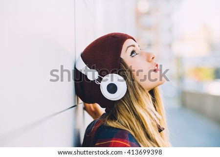 Half length profile portrait of young handsome caucasian blonde hair woman leaning against a wall, listening music with headphones, looking up - serene, enjoying, music concept - stock photo