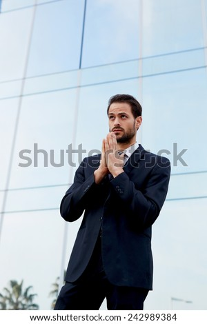 Half length shot of a worried business man standing near office building - stock photo