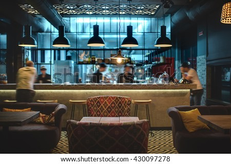 Half-lighted hall in a loft style in a mexican restaurant with open kitchen on the background. In front of the kitchen there are wooden tables with multi-colored chairs and sofas. On the sofas there - stock photo