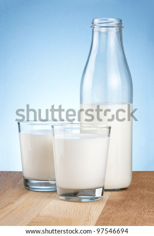 Half Milk bottle and two glass is wooden table on a blue background - stock photo