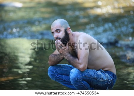 half naked, bearded bald man washing his face with fresh water in nature