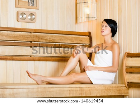 Half-naked girl relaxing in sauna. Concept of self-care, health and relaxation - stock photo