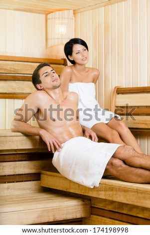 Half-naked man and young woman relaxing in sauna. Concept of self-care, health and relaxation - stock photo