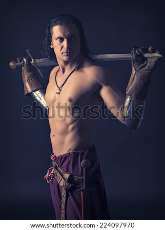 half-naked man with a sword in medieval clothes on a dark background - stock photo
