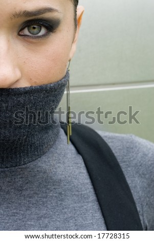 Half of a brunette beauty's face with a turtleneck covering her mouth - stock photo