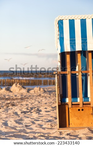 Half of a locked beach chair in the sand at the end of the summer season/End of the Beach Season