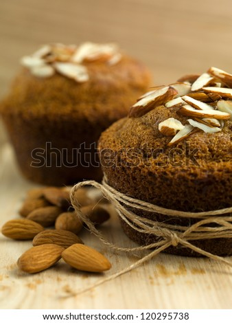 half of a muffin, wrapped up in string, on a wooden board, with a bunch of almonds beside it, with another muffin in background - stock photo