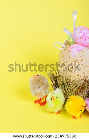Half of big easter egg and small chickens over yellow paper - stock photo