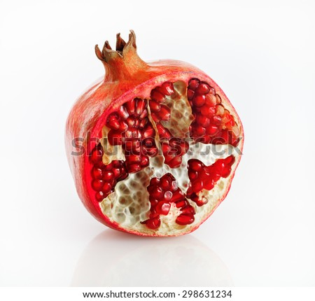 Half of fresh ripe tasty pomegranate on a light background with reflection. Studio shot. - stock photo