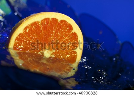 Half of grapefruit in water on a blue background.