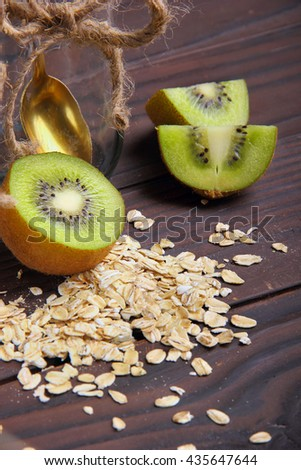half of kiwi and quarter  with empty jar and oat flakes - stock photo
