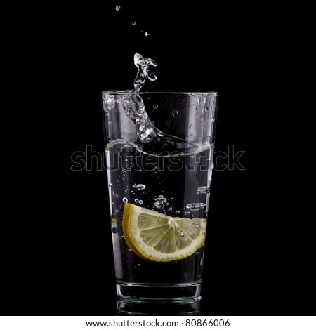Half of lemon falling down in glass with water on deep black.  Beautiful glass with sparkling water or other transparent drink and a slice of lemon on black background - stock photo