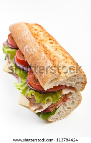 Half of long tasty subway baguette sandwich with lettuce, tomatoes, ham, turkey breast, salami and cheese - stock photo