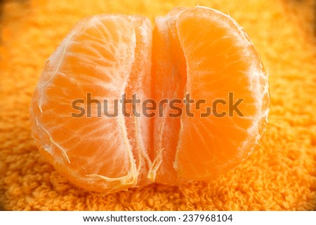 Half of mandarin or tangerine on the orange background